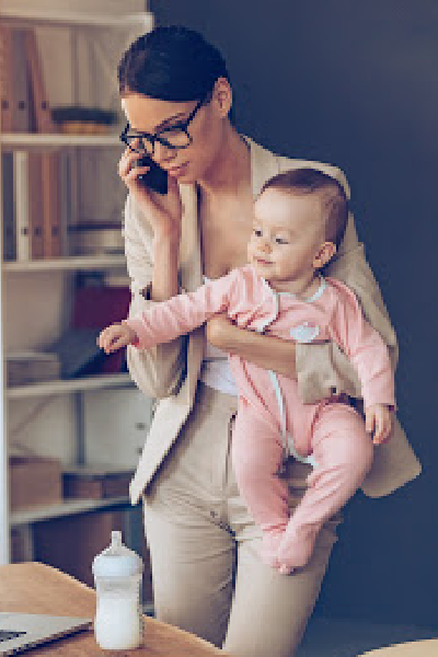 Mom juggling work at home while holding a baby