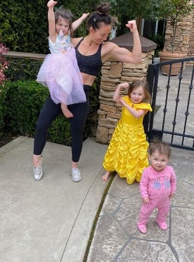 mom showing strong arms with her daughters