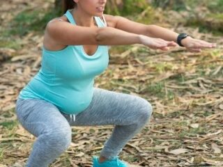fit pregnant mom squatting in nature
