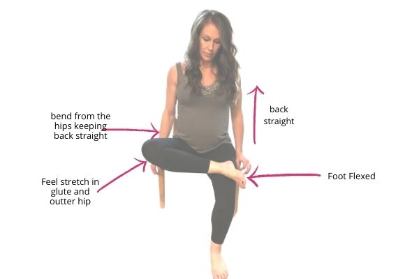 fit pregnant mom doing a seated pigeon pose for pregnancy back pain stretch