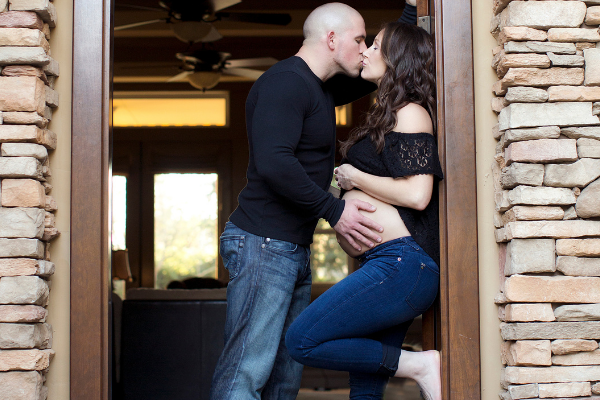 dad kissing pregnant mom with his hand on her belly