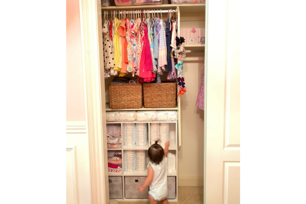 little girl standing in front of her closet that is organized