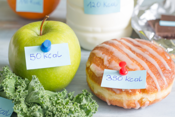 a green apple and donut with calorie information