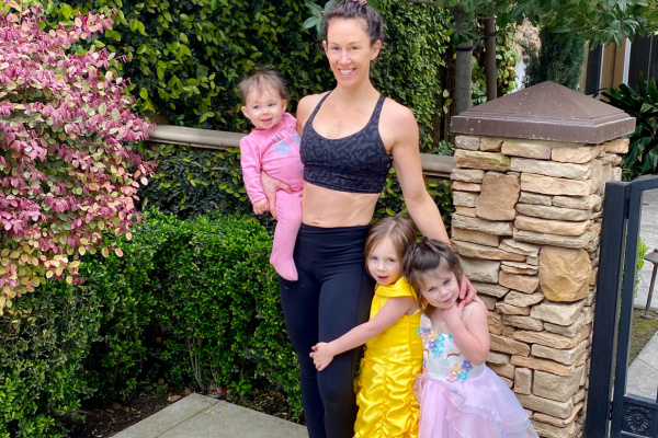 fit mom in black workout clothes taking a picture with her three daughters