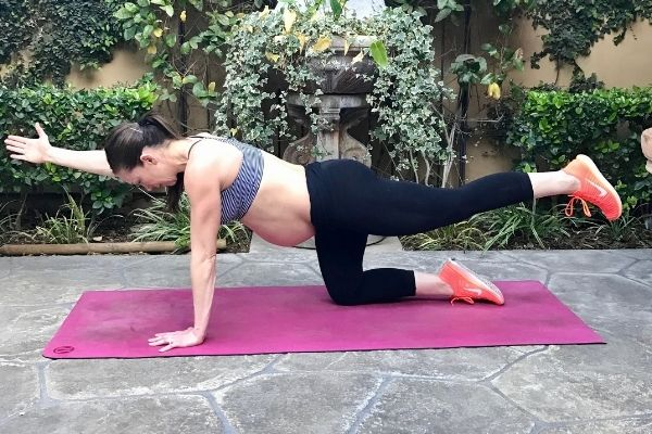 fit pregnant mom in a striped sports bra and black pants doing a bird dog exercise for core strength