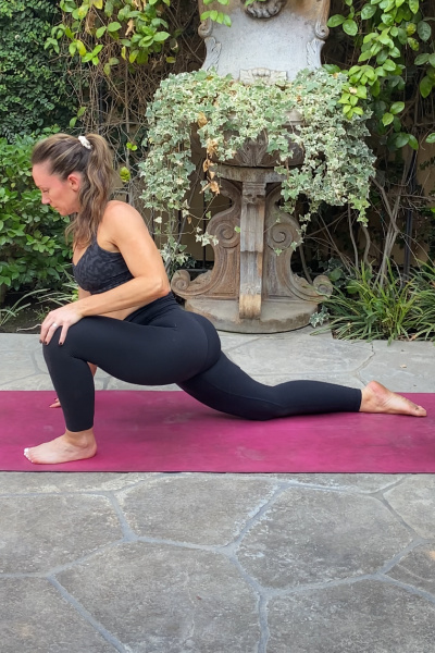 pregnant mom in black pants on a pink yoga mat in a deep lunge stretch to help her body prepare for labor