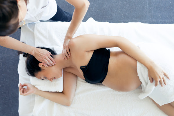 pregnant mom in a black tube top bra lying on her side getting a neck massage
