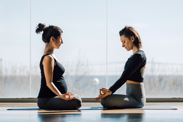 a pregnant women and non pregnant women sitting on the floor meditating with good posture