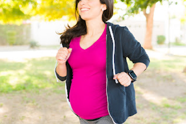 Active pregnant woman in her 30s smiling while walking in the park to stay healthy and fit during her pregnancy